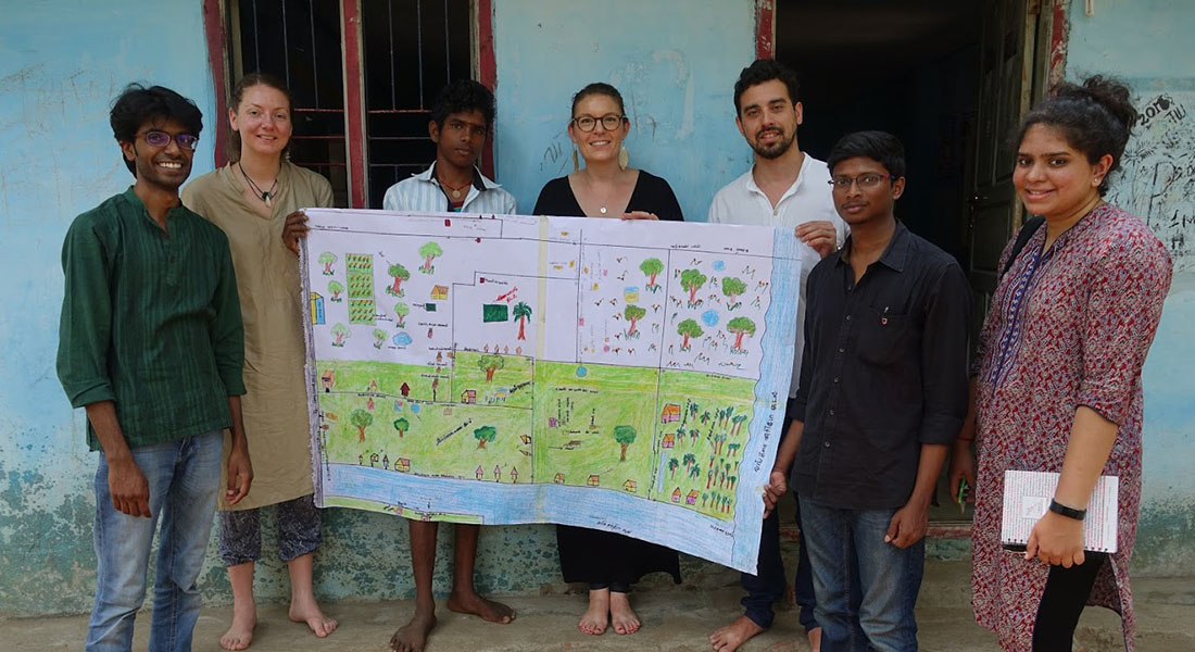 7 people standing, showing a hand-drawn planning of a rural community in India